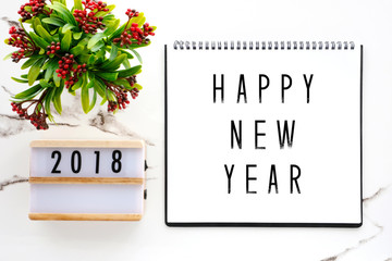 2018 new year greeting card, 2018 on wood box and happy new year on notebook paper over white marble background, banner, top view