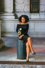 African American Woman seeking love in New York. Wearing long sleeve, off shoulder dress, holding white rose, young black girl sitting on metal pillar on street, crossing legs, looking down, thinking