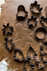 cut out gingerbread man with dough with cookie cutters top view