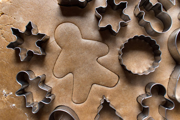 cut out gingerbread man with dough with cookie cutters