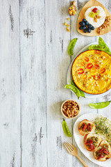 Vertical top view of healthy lunch or dinner on white table with copy space. Frittata with young peas, bruschetta with tomato and pesto, cheese plate.