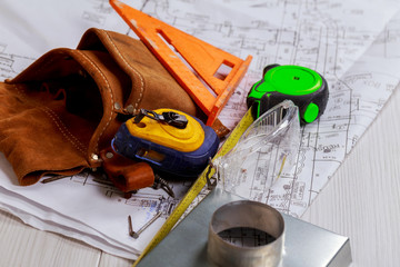 Worker equipments on workplace. paper knife and tape measure. Construction design. Paper engineering plans.