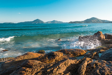 blue sky and sea water hitting the stones of the beach praia grande brazil