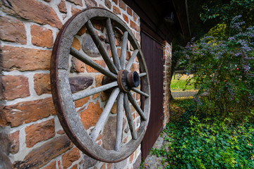 A wooden wheel from a cart hangs on a brick wall.