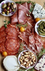 Charcuterie board with meat, cheese, pickles and olives