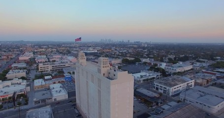 Fotobehang - Aerial view American US flag waving on rooftop city Los Angeles cityscape sunset