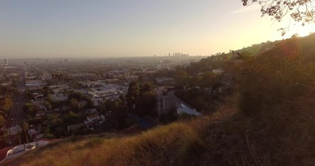 Fotobehang - Aerial shot of city of Los Angeles flying from Hollywood Hills at sunset. 4K UHD