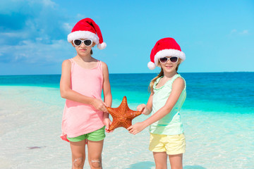 Adorable little girls on Christmas beach vacation.