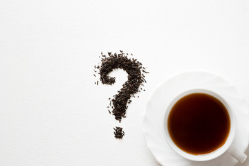 Question mark created from black, dried, loose tea with cup on the white table. Choice of the best sort and quality tea. Empty place for a text.