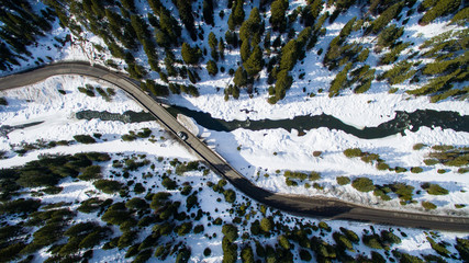 aerial view of a road over a snowy river.