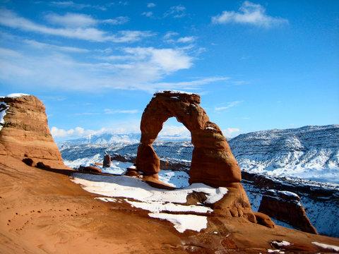 snowfall over famous utah landmark delicate arch.