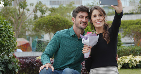 Woman receiving a bunch of flowers and taking selfie on cellphone