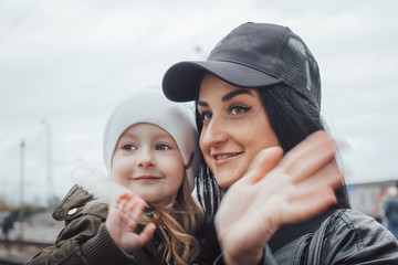 Portrait of a brunette mom in a cap and little girl in a white hat