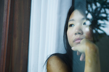 young sad and depressed Asian Chinese woman looking thoughtful through window glass suffering pain and depression in sadness concept