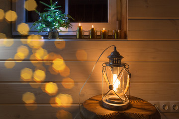 Christmas window decoration with red burning candles and a lantern for a background.