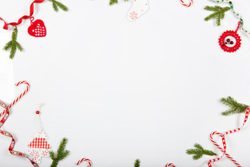 Christmas holiday composition. Festive creative red pattern, xmas handmade decor holiday with ribbon, Christmas candy canes, gift, christmas tree and red decorations on white background.