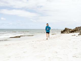 Young man running along seaside