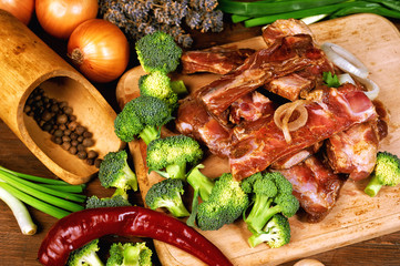 Raw pork ribs with vegetables on a wooden table
