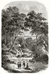 Magnificent natural scenario in the luxuriant jungle with a bamboo bridge built by Dayak people, western Borneo. Created by De Bar after Keppel published on Le Tour du Monde Paris 1862