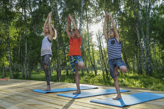 Young woman and kids performing yoga in park on a sunny day