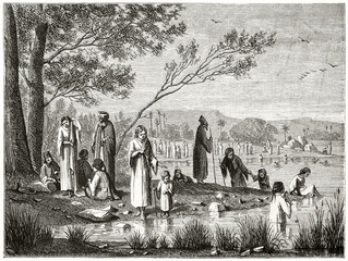 Ancient white dressed greek pilgrims getting rest under trees on the banks of Jordan river. Men, women and child. Created by Riou and Gusmand published on Le Tour du Monde Paris 1862