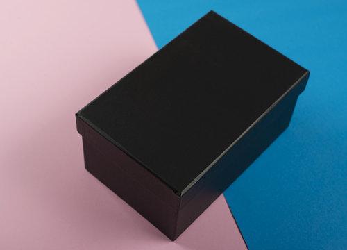 Shoe box of black color on pink and blue background. Mockup.