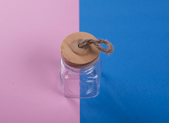 Glass jar with wooden stopper on pink and blue background.