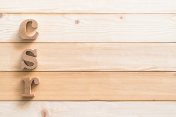 CSR (Corporate social responsibility) abbreviation wood letters on wooden background for business concept backdrop
