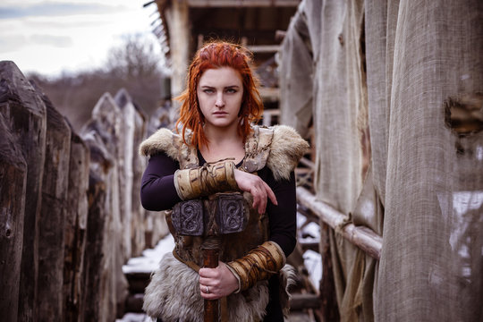 Viking woman with hammer in a traditional warrior clothes.