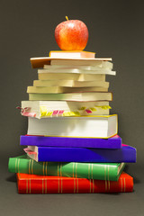 Concept of education. Stack of school books with a red apple on top in front of dark gray background