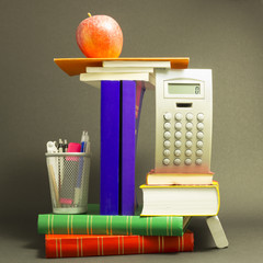 Concept of education. Stack of school books with calculator, marker and pencils and a red apple on top in front of dark gray background