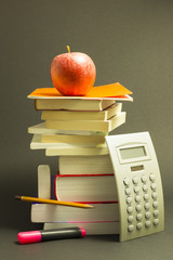 Concept of education. Stack of school books with calculator, pink marker and pencil and a red apple on top in front of dark gray background