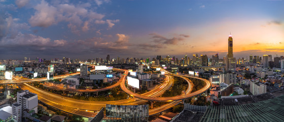Panoramic Bangkok City with Curved Express Way and Skyscraper. Top View of City Elevated Highway with Car Traffic Light Trial at Twilight Time.