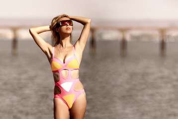 Super model girl with blond hair in sun glasses in sexy pink bikini swimsuit with hands in hair at the beach with sea background, shallow depth of field portrait. Recreational time at summer vacation