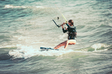 Kite surfing girl in sexy swimsuit with kite in blue sea riding waves with water splash.