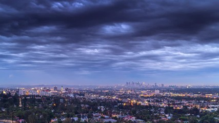 Fototapete - Cloudy sky over city of Los Angeles cityscape dusk to night. 4K UHD Timelapse