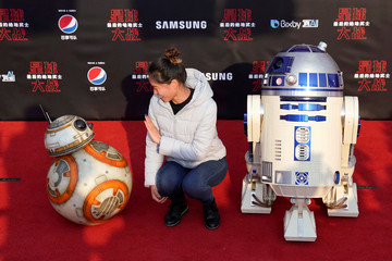 A woman poses for pictures with Star Wars robots R2-D2 and BB8 at the China premiere of 'Star Wars: The Last Jedi', at the Shanghai Disney Resort in Shanghai