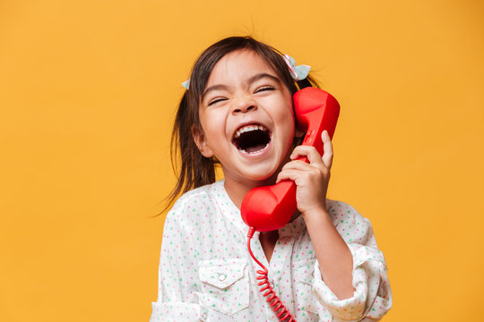 Screaming excited little girl child talking by red retro telephone.