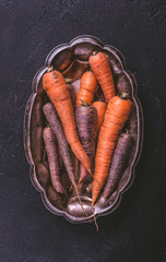 Orange and purple raw carrots in vintage tray on dark background top view