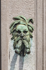Old medieval drinking fountain in the form of a male head with snakes in his mouth in Bruges Belgium