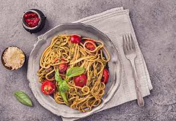 Spaghetti pasta with pesto and cherry tomatoes on concrete background, top view