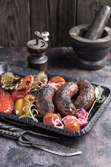 Rustic homemade sausages with grilled vegetables on table