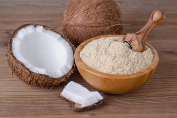 coconut flour in a bowl with scoop on brown wooden background