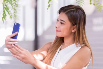 Beautiful women are happily selfie in garden. Selected focus