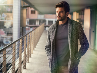 One handsome young man in urban setting in European city, standing - fototapety na wymiar