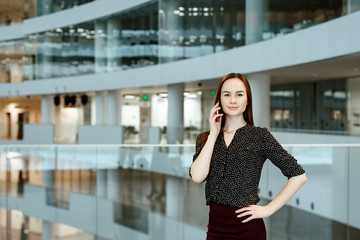 The young business woman talks on the smartphone against the background of office.