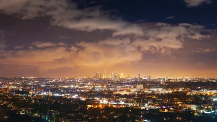 Fotobehang - Cloudy storm sky over city Los Angeles cityscape night Zoom out downtown skyline