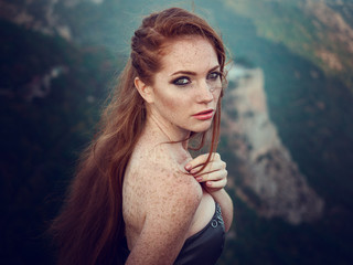 Summer outdoors portrait of beautiful furious scandinavian warrior ginger woman in grey dress with metal chain mail.