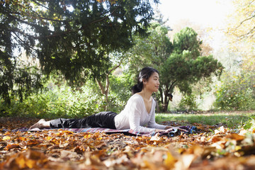 Smiling woman performing yoga while lying on picnic blanket at park during autumn