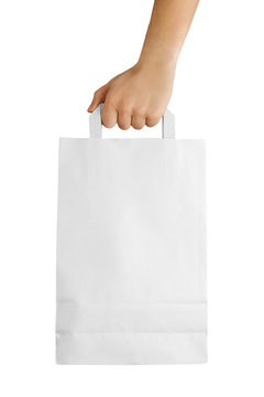 Male hand holding white paper bag isolated on white